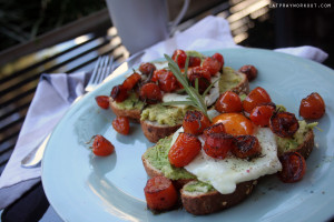 fresh gourmet egg, avocado and rosemary balsamic tomatoes on toast