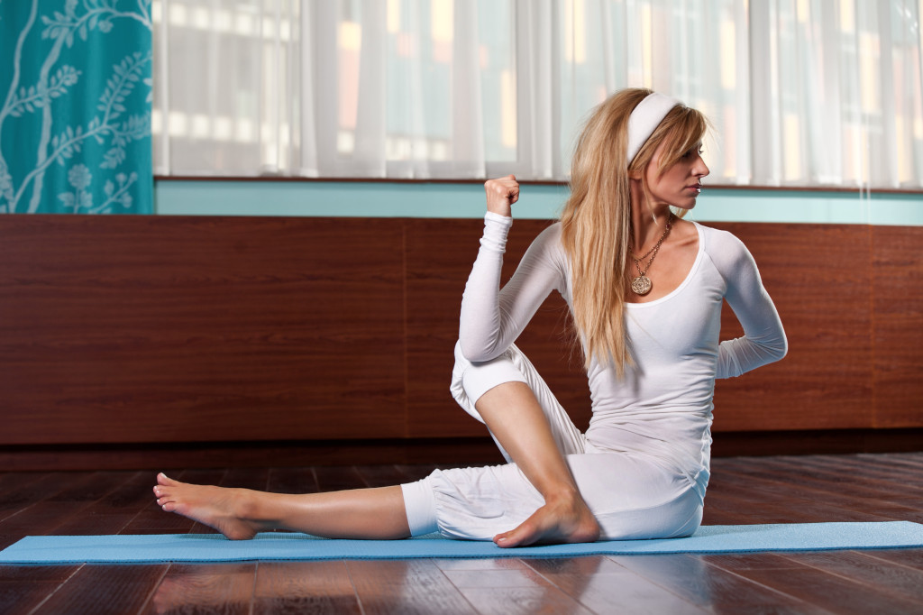 yoga twist static stretch by girl in white activewear