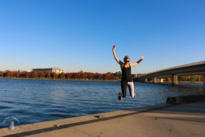 Athlete runner jumping at Lake Burley Griffin in Canberra winter wearing skins