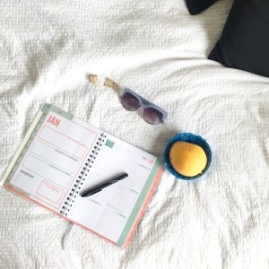 2017 Collins lifestyle diary peach colour on bed with bowl of fruit, pen and sunglasses