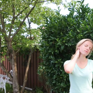 Amy, Australia top health blogger Eat Pray Workout outside massaging sore neck