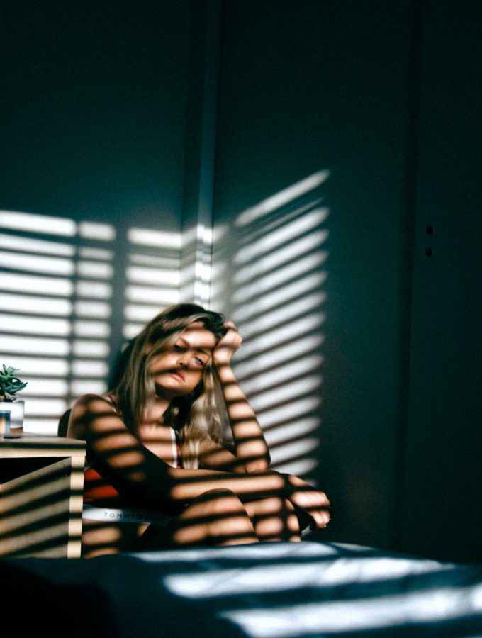tired girl in dark bedroom with light streaming through window blinds