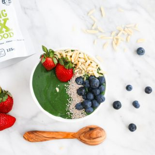 bright green healthy smoothie bowl with strawberries, blueberries, seeds and nuts