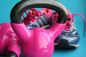 pink dumbbell weights with pink and blue sneakers