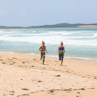 females running and exercising at beach in summer