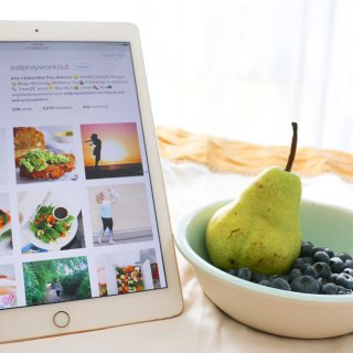 hand holding iPad in bed with @eatprayworkout instagram open with a bowl of fruit, pears and blueberries
