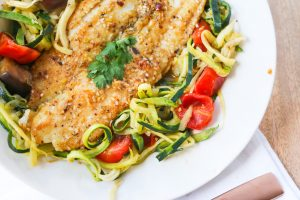 plate of dukkah fish on tomato and eggplant zoodles