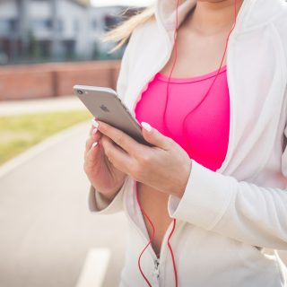female listening to music while exercising outdoors