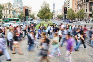 busy crowd walking through city blurred