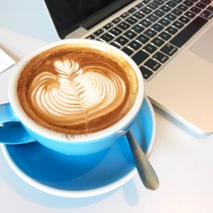 cup of coffee and laptop in cafe