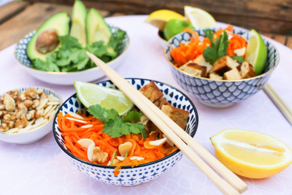 Fresh asian tofu bowl of carrots pumpkin lime herbs and noodles