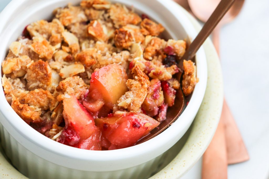 Healthy baked dessert of apple and raspberry crumble topping