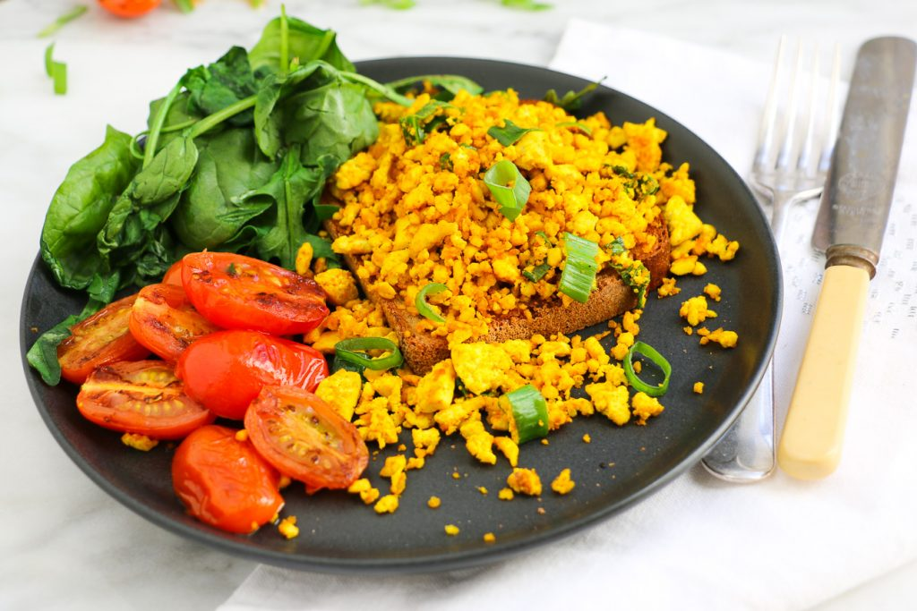 Fresh scrambled tofu made with almond milk on toast with salad of cherry tomatoes and green leafy vegetables for Eat Pray Workout, Australian top health blog