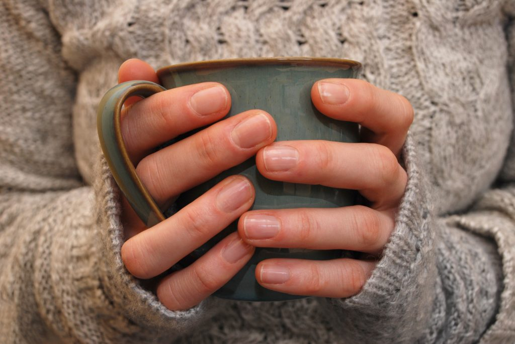 Closeup of a woman's hands holding a mug of drink
