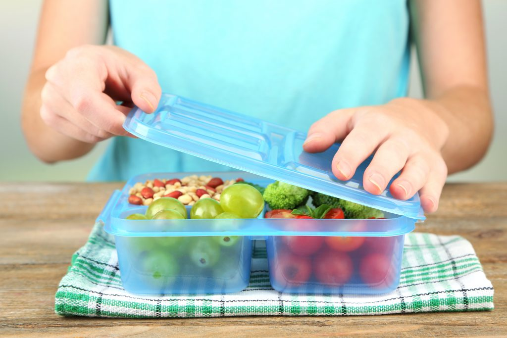 girl preparing snack lunch box with fresh fruit vegetable and nuts in kitchen
