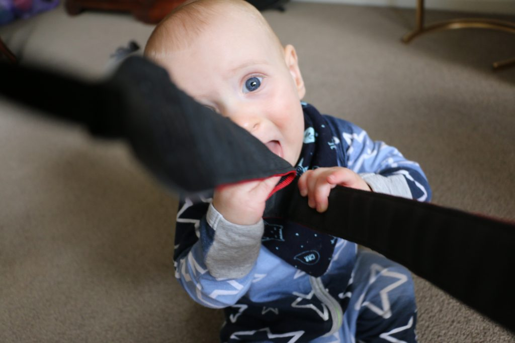 baby boy blue eyes pulling at camera strap mum blogger eat pray workout