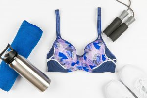 bright blue and purple colourful pattern berlei sports bra with exercise skipping rope water bottle gym towel and running shoes