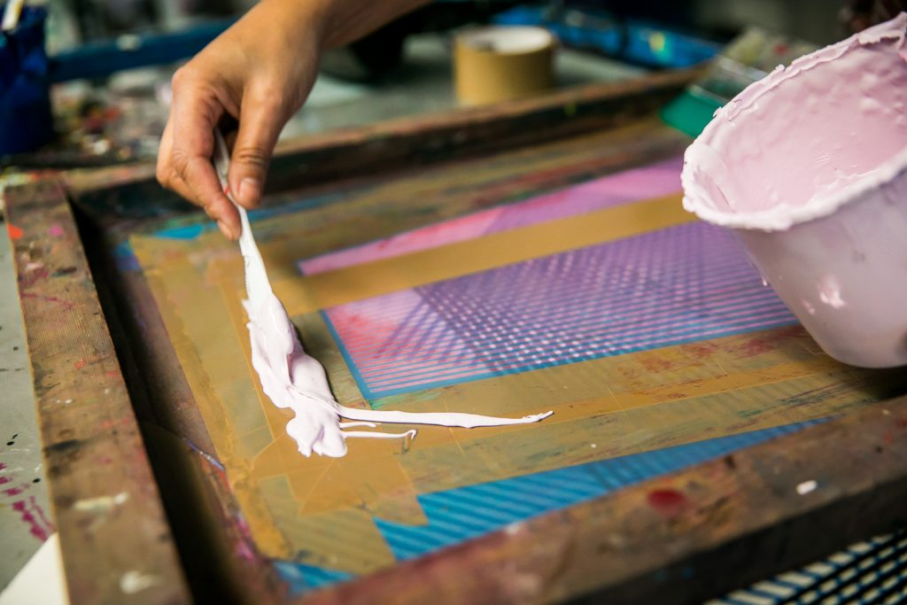 Artist Kate Banazi in her art screen printing studio laying light pink paint onto a screen print painting