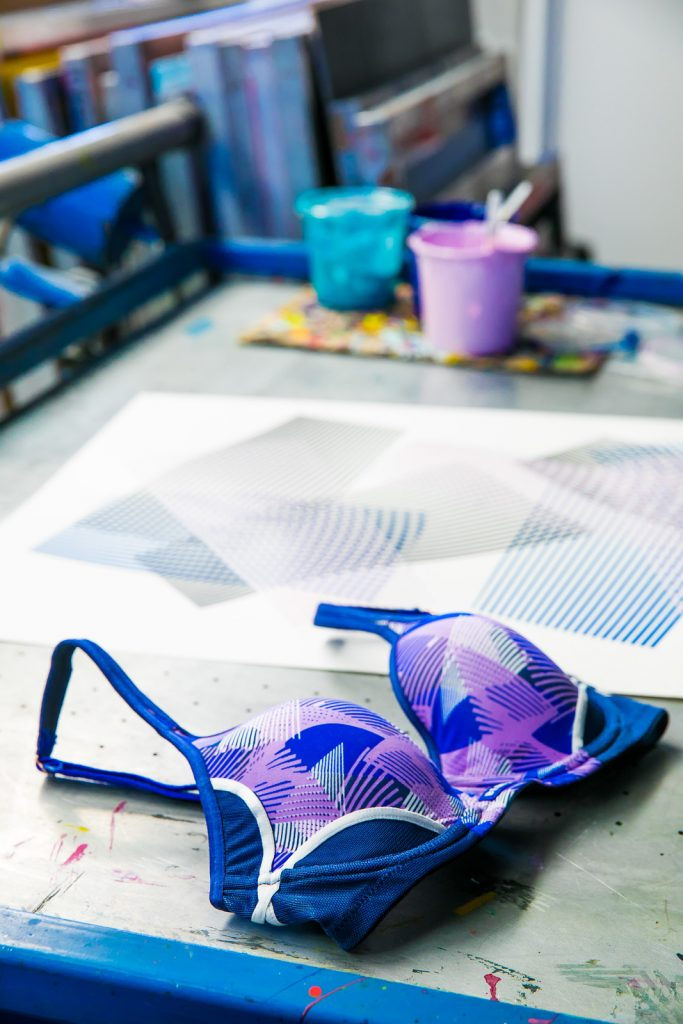 Kate Banazi collaboration with Berlei Sports Bras purple and blue screen printed line design next to original artwork