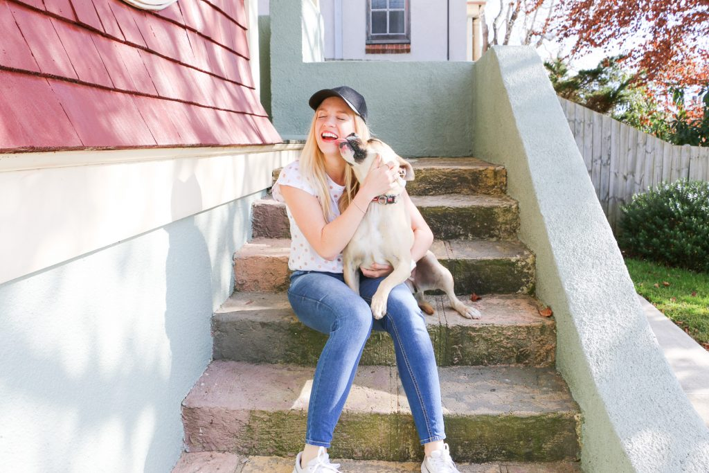 Photo of smiling blonde Amy Australian top health blogger Eat Pray Workout blog and pet dog Honey in the garden at Burnbank House Wentworth Falls Blue Mountains