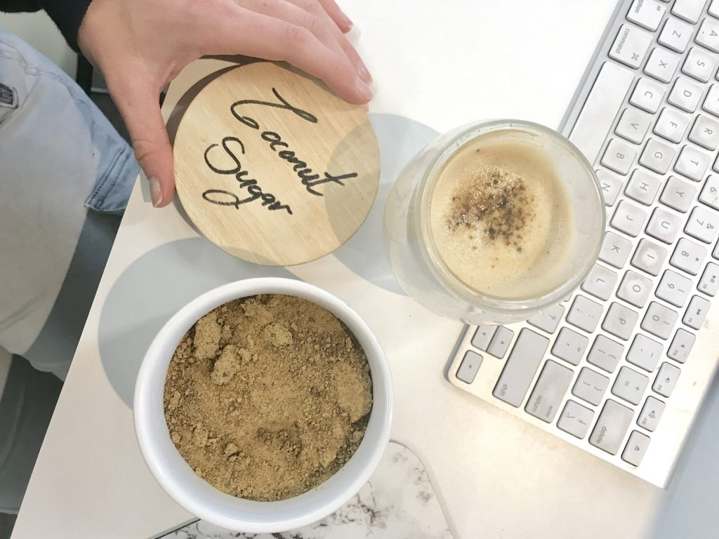 coconut sugar in bowl next to coffee cup and keyboard