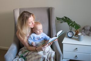 Eat Pray Workout Australia top health blogger Amy with baby boy Finn sitting in rocking chair with Waverly Mills wool blanket in nursery reading book in the morning