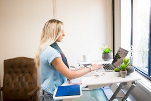 Eat Pray Workout Australia top health blogger parent Amy Darcy working on her laptop and Standing Varidesk in home office study