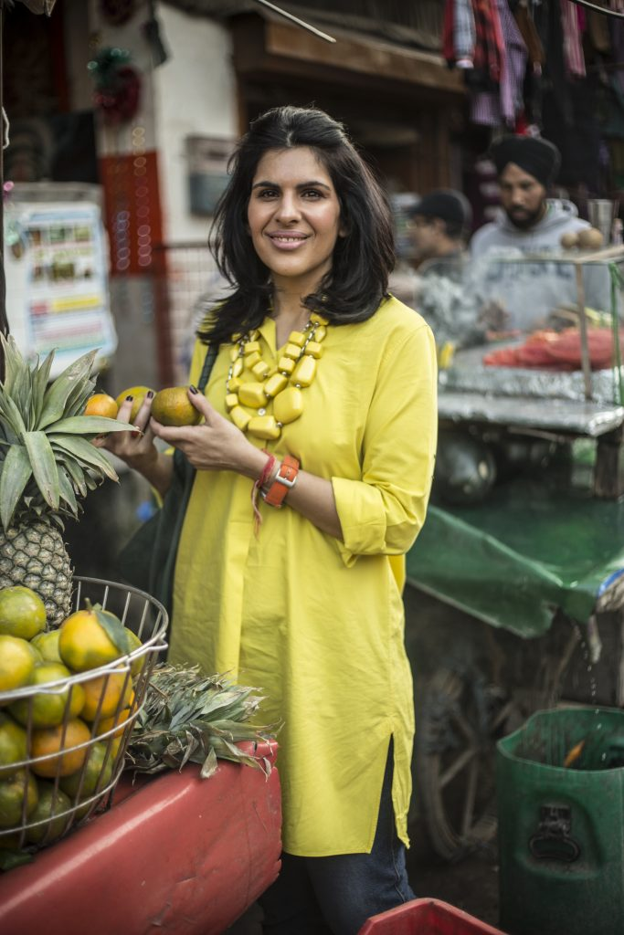 how to make indian healthier with celebrity chef Anjum Anand in yellow dress with oranges and pineapple in india