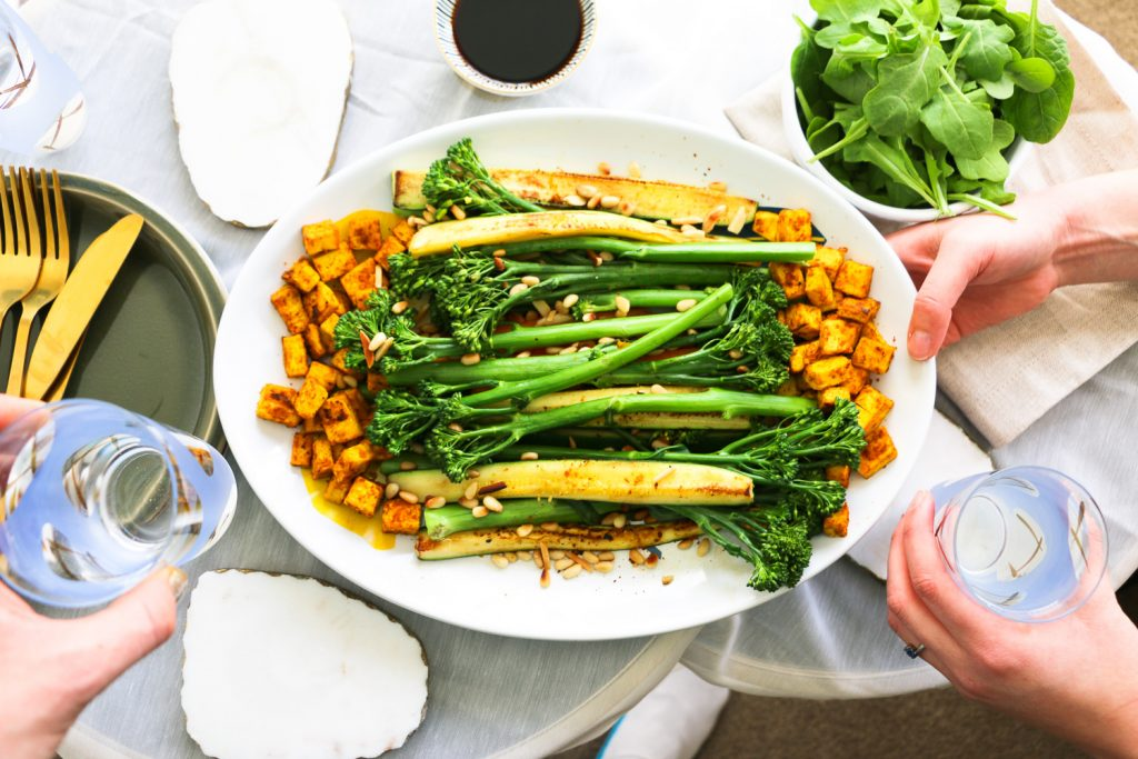 Broccolini, Zuchinni & Tumeric Tofu Salad with hands on table set with glasses flat lay