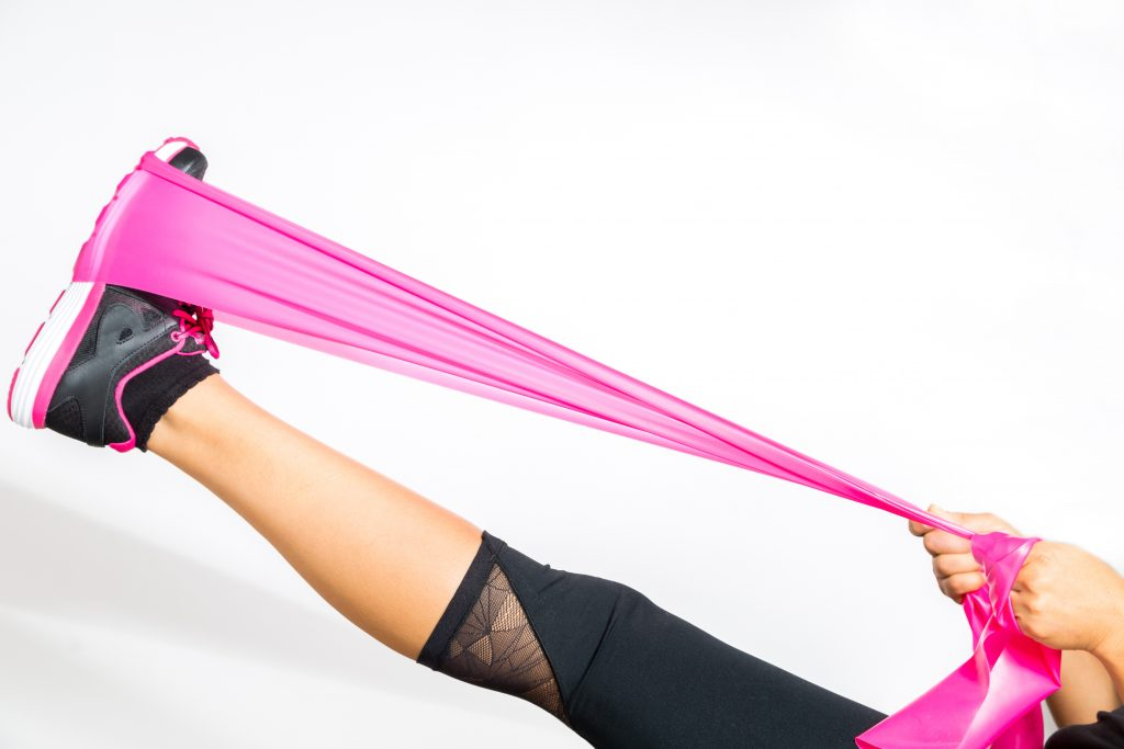static stretching girl with pink elastic band post workout in activewear