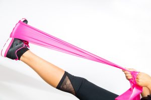 woman stretching with pink band