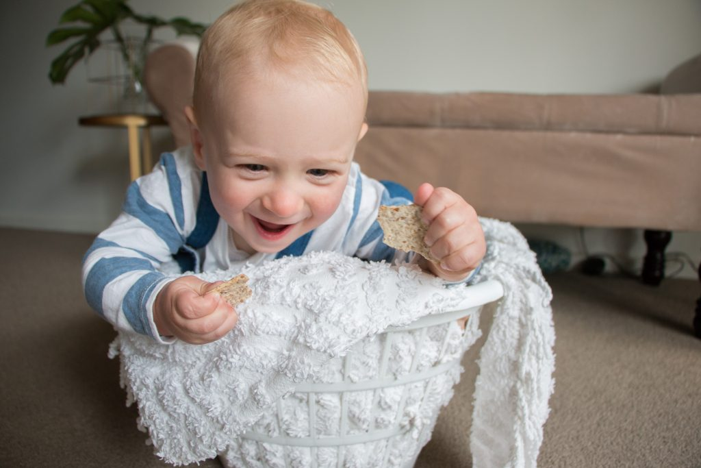 15 month old Finn baby toddler in washing basket with linen smiling holding biscuits eat pray workout