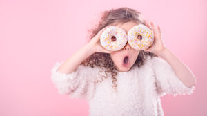 Portrait of a little surprised girl with curly hair, and two mouth-watering donuts in her hands, closes her eyes with donuts, on a pink background