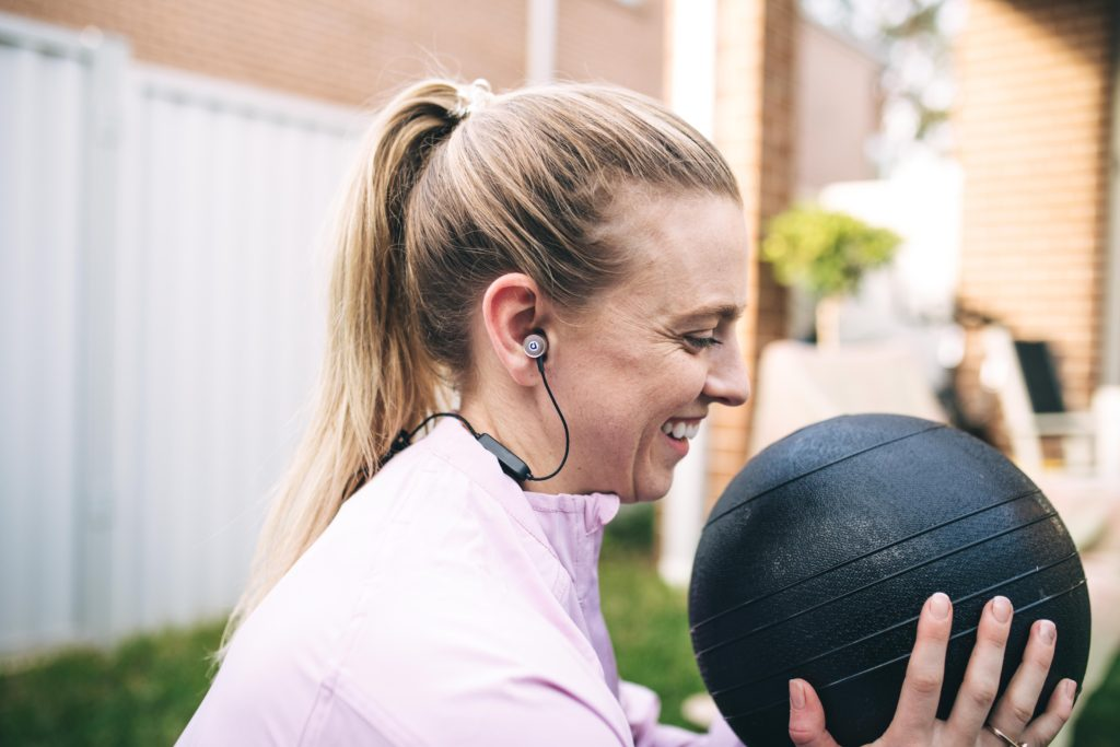 Amy Darcy blonde with med ball smiling in squat showing motivation to exercise regularly
