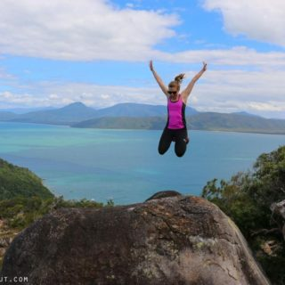 Amy jumping on rock at top of mountain with view of water in the background during holiday in Thailand
