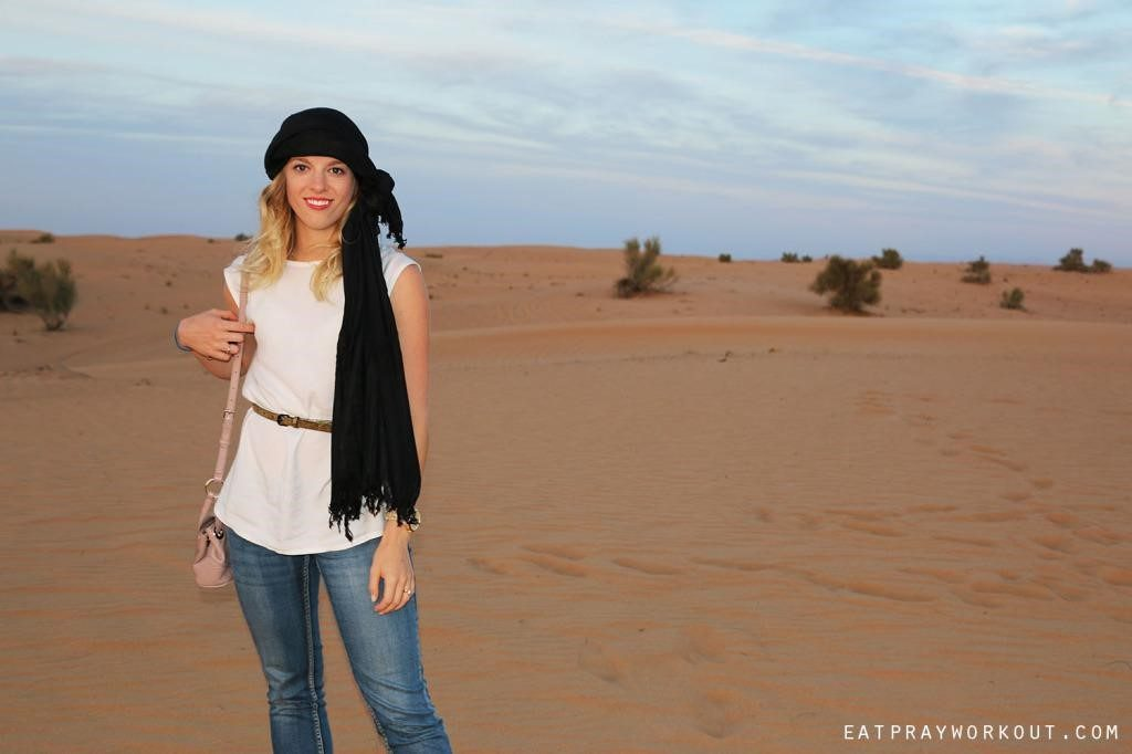 Amy pictured infront of dessert in Dubai, dressed with headscarf.