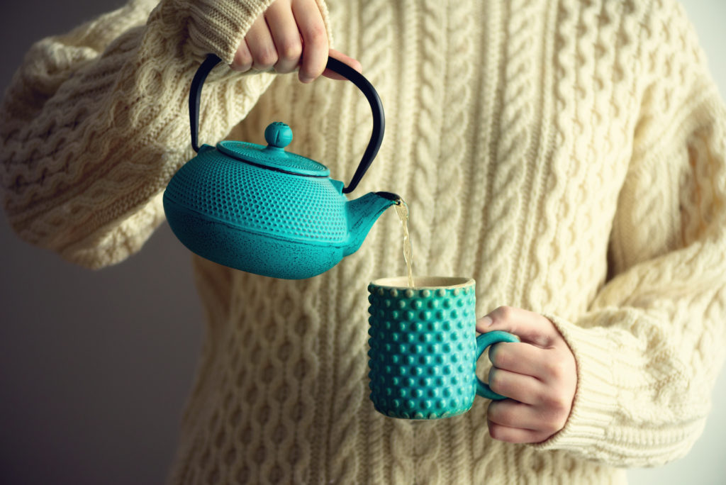Woman in warm knitted woolen sweater holds turquoise teapot and pouring herbal tea into handmade cup. Copy space. Winter and Christmas holidays concept. Banner.