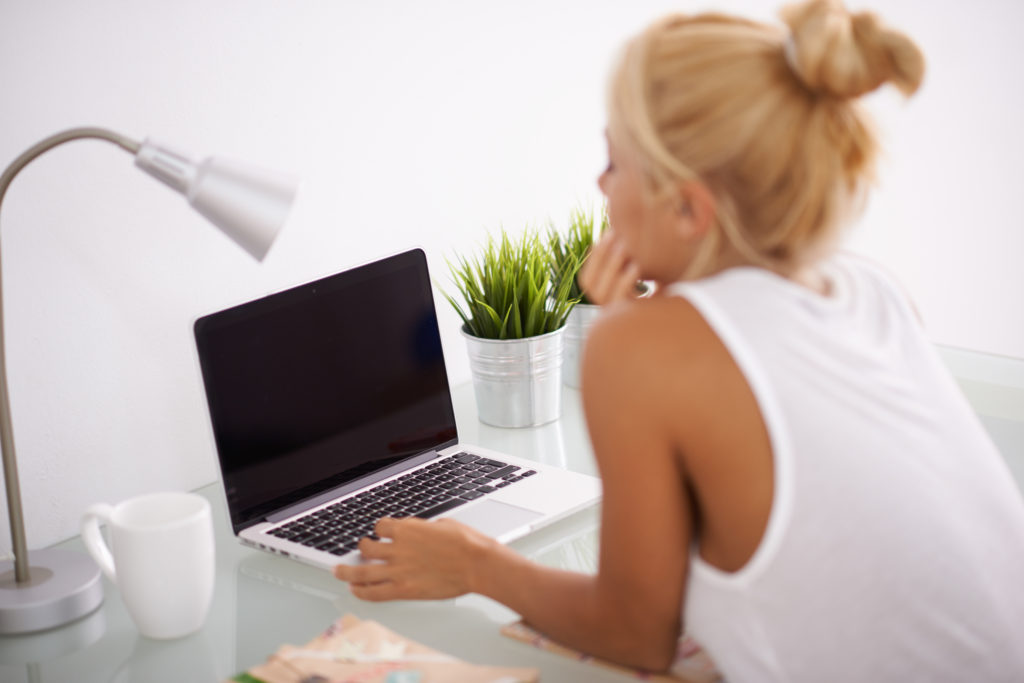 Blonde woman at her workspace Manage Stress as a Small Business Owner