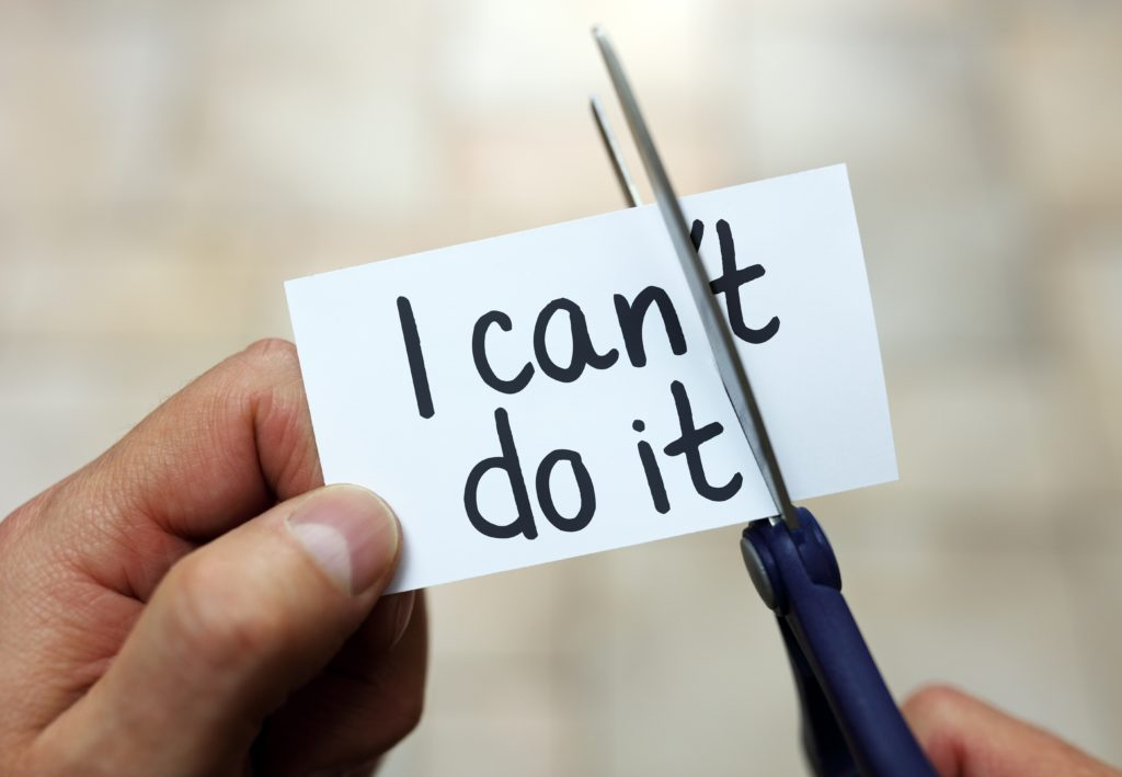 Man using scissors to remove the word can't to read I can do it concept for self belief, positive attitude and  motivation. How to Optimise Your Thinking to Achieve Your Goals