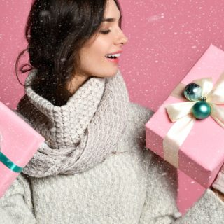 Portrait of a happy casual young woman isolated over pink background, holding stack of gift boxes