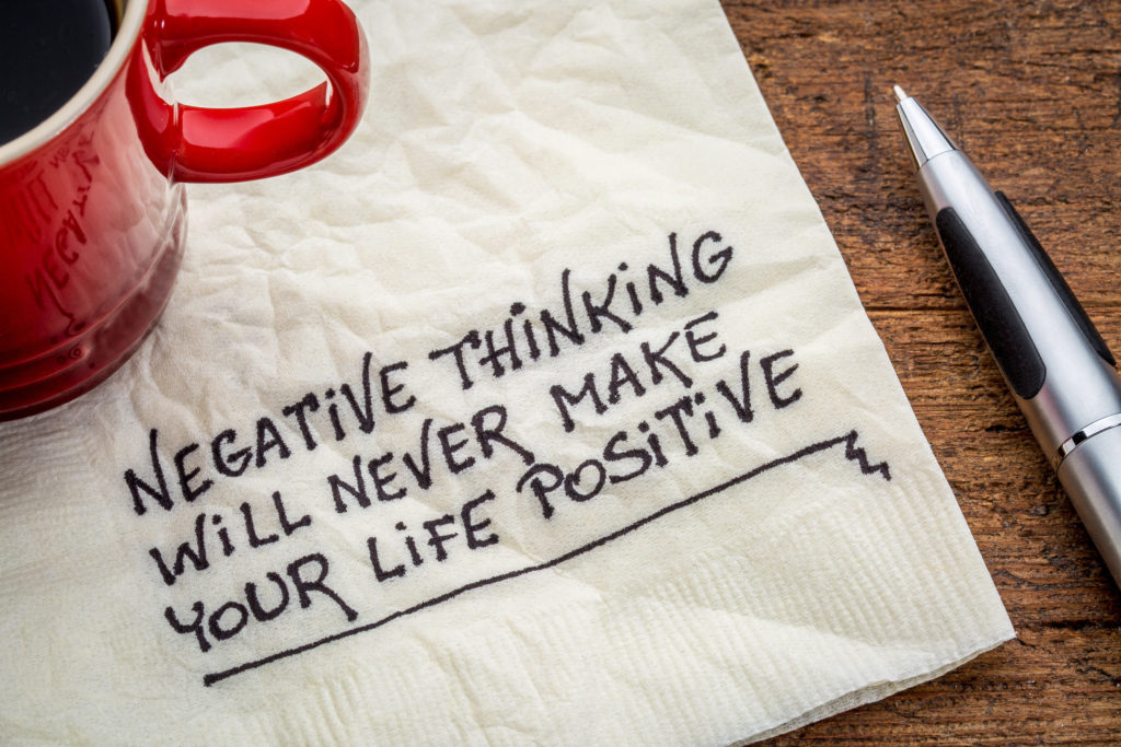 How to Optimise Your Thinking to Achieve Your Goals. negative thinking will never make your life positive - inspirational handwriting on a napkin with a cup of coffee