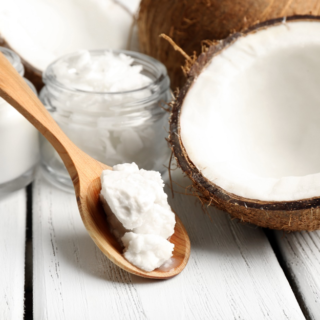 What's the difference between good and bad fats half coconut with coconut oil on wooden spoon