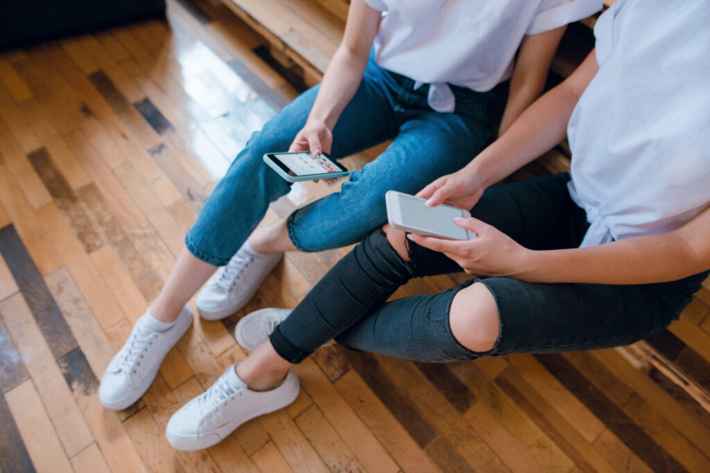 Top view of two young girls, friends sitting on the sofa and using their smartphones. Scrolling the instagram.