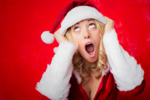Woman in horror pulling her red Santa hat