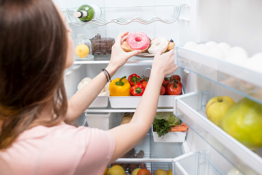 Woman taking sweet donuts from the refrigerator