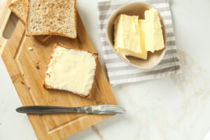 Composition with tasty toasts and butter on table