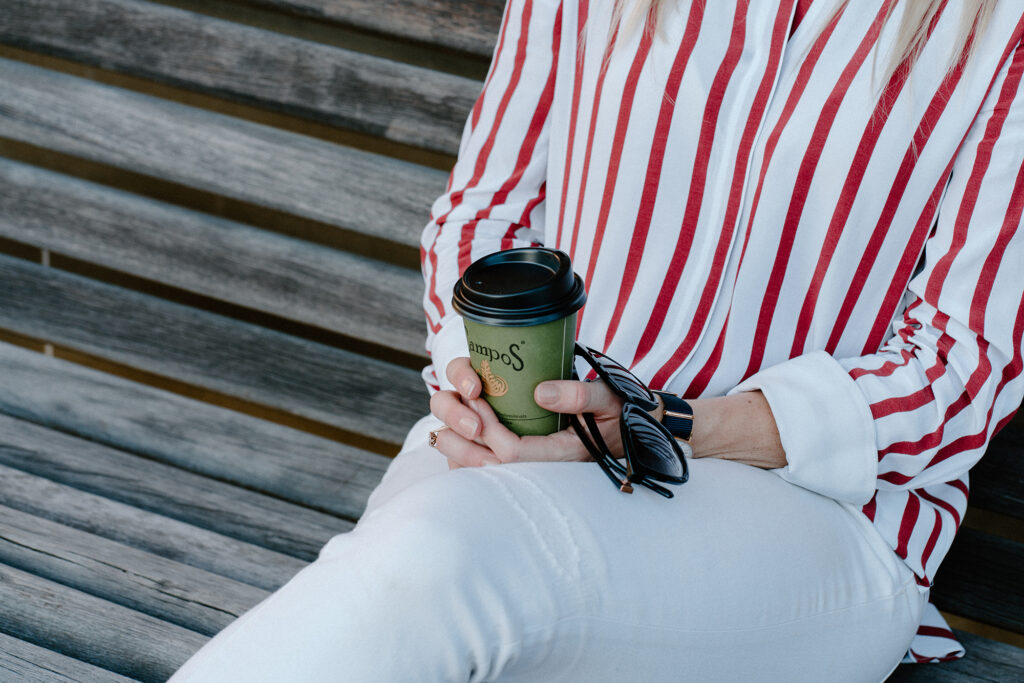 red white stripe shirt coffee while pants on bench