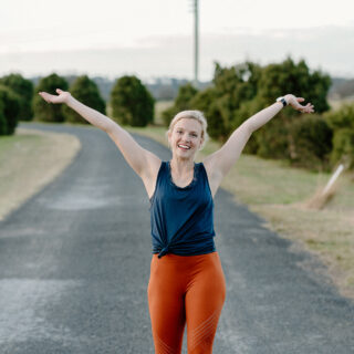 Amy orange tights black top arms in air after running
