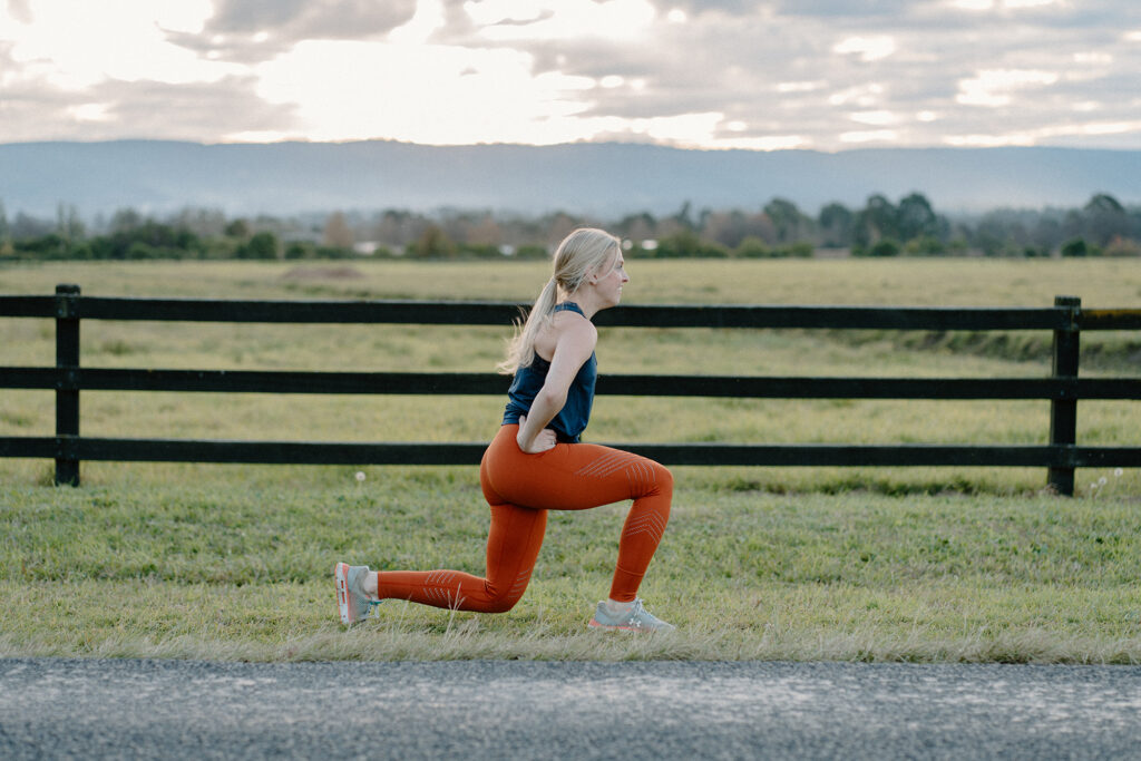 Amy in orange tights and black workout top doing walking lunge exercise
