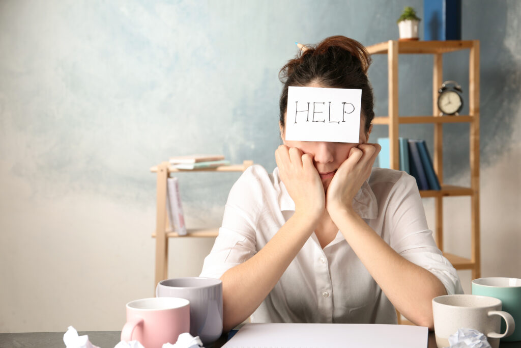 how to avoid burnout Young woman with note HELP on forehead at workplace.
